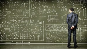 Business person standing against the blackboard with a lot of da