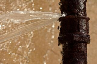 bigstock-Rusty-burst-pipe-leaking-water-109170257.jpg