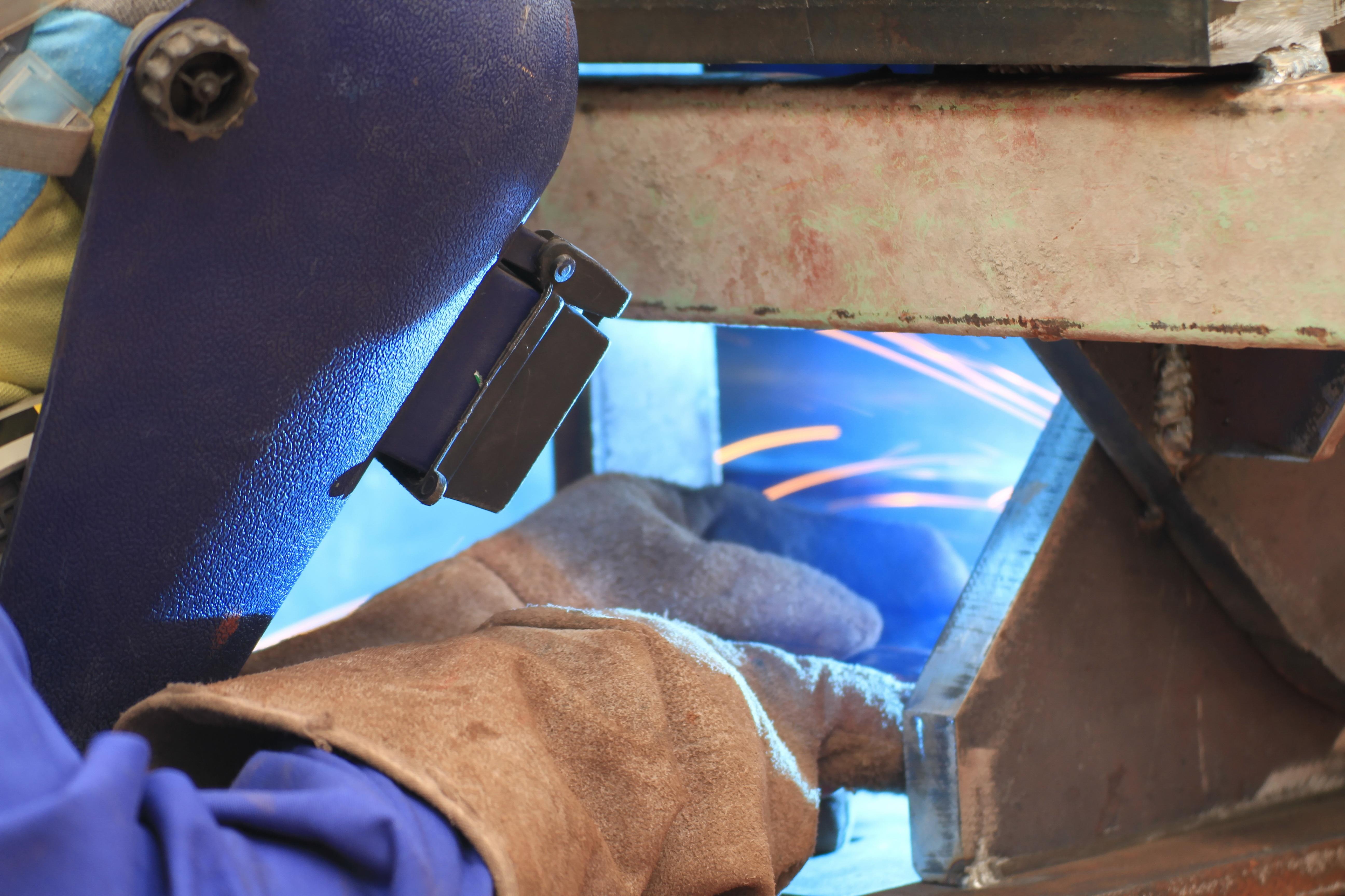 bigstock-welder-is-welding-steel-struct-85553387