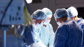 Surgeons in operating room with air quality monitors on.