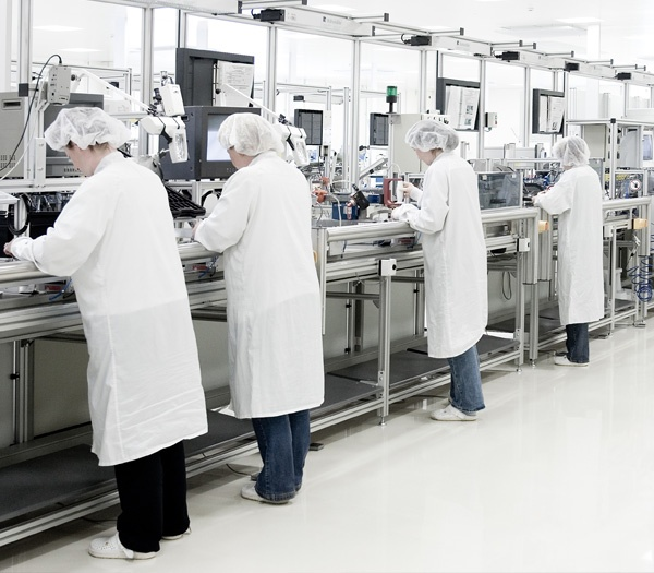 Assemblers in a clean room environment that is being monitored by particle counters.